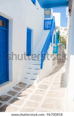 Narrow streets with white houses, ladders and blue windows and balconies on the islands of the Mediterranean. Mykonos. Greece.