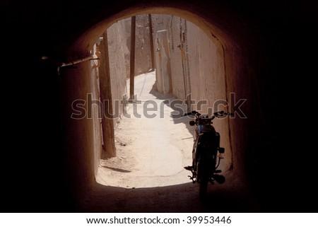 Narrow urban path in Yazd, small dark tunnel and motor bike. Iran - stock photo