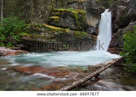 Narrow waterfall passes through rocky moss covered gorge in Glacier National Park, Montana.