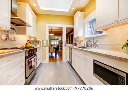 Narrow white and yellow kitchen with skylight and grey floor.