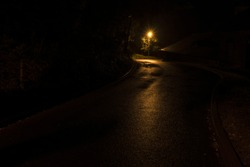 Narrow winding street in the old town with backlit sidewalks. Night shooting, the roof of the house and the street lamp after the rain.