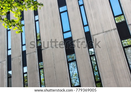 Narrow windows of old fashioned office building. Windows with reflections of skies and trees. Grooved concrete facade with windows. #779369005
