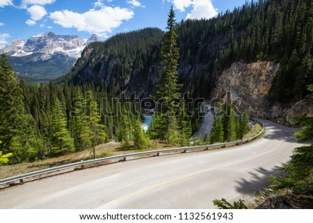 Narrow windy road in the Canadian Rockies during a vibrant sunny summer day. Located in Yoho National Park, British Columbia, Canada.