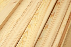 Narrow wooden slats or boards in close-up lie in a stack. This is a noble polished wood in the carpentry shop. Background or screen saver for advertising a range of construction products.