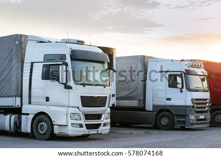 Narva, Estonia - August 20, 2016: Heavy trucks loaded with goods trailers, parked in waiting area on state border crossing. International hard transportation and logistics. Transport infrastructure #578074168