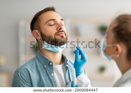 Nasal coronavirus PCR test. Doctor using swab stick to take covid virus specimen from potentially infected young guy at home. Viral disease prevention and diagnostics concept