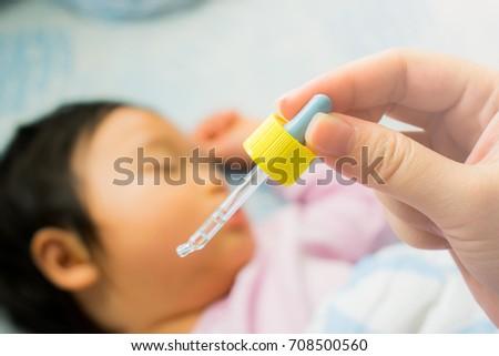 Nasal instillation for baby. Nasal instillation of medication. Nose drops.  Ear instillation for baby. Ear instillation of medication. Ear drops.  Close-up mother's hand holding dropper.