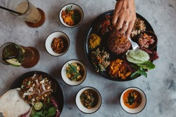 Nasi Campur, asian dish made of brown rice and mixed variety of vegetables, tofu, tempeh, fritters and sauces, asian Indonesian cuisine, food culture, spicy
