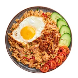 Nasi Goreng - Indonesian Chicken Fried Rice on black plate isolated on white backdrop. Nasi Goreng is an Indonesian cuisine dish. Balinese Food. Asian meal. Top view