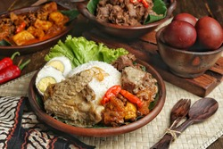 Nasi Gudeg, a traditional dish from Yogyakarta and Central Java, Indonesia. White rice mixed with Gudeg, Krecek Fried Sambal, Pindang Egg and Chicken Opor. Served on earthenware plate.