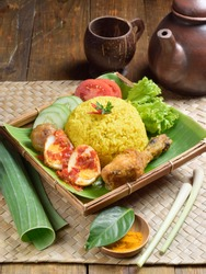 Nasi kuning, yellow steamed rice, cooked with tumeric, coconut milk, lemon grass and bay leave. Served as celebrate special moment in Javannese people.  Can be served for breakfast