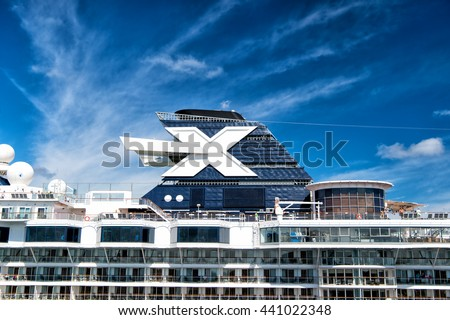Nassau, Bahamas-January 29, 2016: Sign of Celebrity cruise lines on top of Large luxury cruise ship on cloudy blue sky background