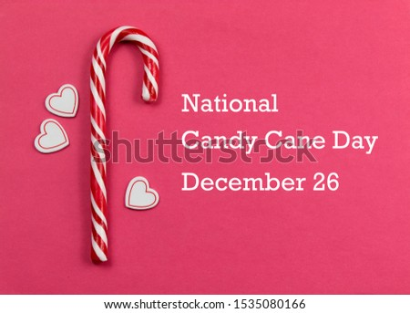 National Candy Cane Day images. Candy Cane with hearts on a pink background. Candy Cane Day Poster, December 26. Christmas candy cane stock images. Sweet Christmas symbol #1535080166