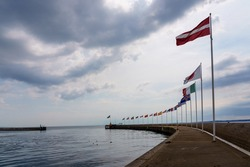 National country flags waving at the pier in the harbor of Helsingborg, Sweden on a cloudy summer day.