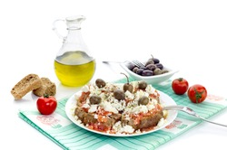 National Cretan, Greek snack (dakos). Crackers with grated tomatoes, feta cheese, oregano, olives and olive oil on a white background close-up.