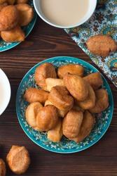 National cuisine - Uzbek baursaki in a plate with a traditional pattern, on a dark wooden table. Bashkir cuisine, Kazakh cuisine. Dastarkhan.