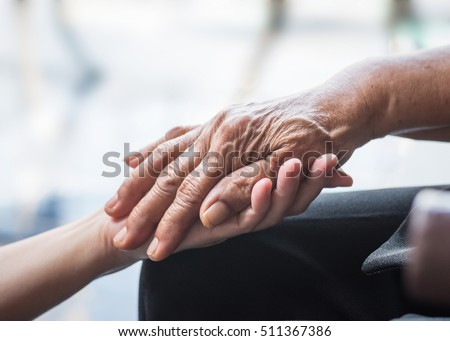 National family care giver month, World Kindness Day concept: Wrinkle hand of Parkinson disease patient/ elderly aging senior citizen person in support of nursing caregiver: Adult day care center week