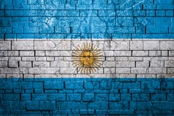 National flag of Argentina on brick  wall background.The concept of national pride and symbol of the country. Flag  banner on  stone texture background.