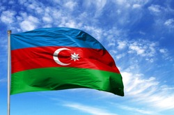 National flag of Azerbaijan on a flagpole in front of blue sky