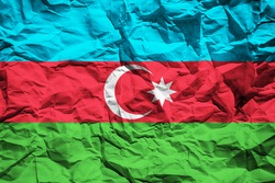National flag of Azerbaijan on crumpled paper. Flag printed on a sheet. Flag image for design on flyers, advertising.