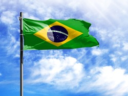National flag of Brazil on a flagpole in front of blue sky.