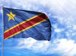 National flag of Congo Democratic on a flagpole in front of blue sky
