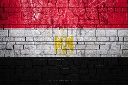 National flag of Egypt on brick  wall background.The concept of national pride and symbol of the country. Flag  banner on  stone texture background.