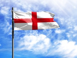 National flag of England on a flagpole in front of blue sky.