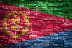 National flag of Eritrea on stone  wall background.The concept of national pride and symbol of the country. Flag  banner on  stone texture background.