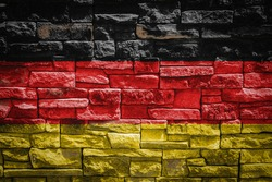 National flag of Germany on stone  wall background.The concept of national pride and symbol of the country. Flag  banner on  stone texture background.