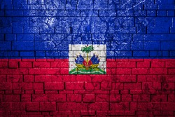 National flag of Haiti on brick  wall background.The concept of national pride and symbol of the country. Flag  banner on  stone texture background.