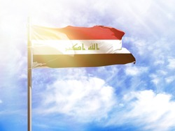 National flag of Iraq on a flagpole in front of blue sky