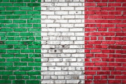 National flag of Italy depicting in paint colors on an old brick wall. Flag  banner on brick wall background.