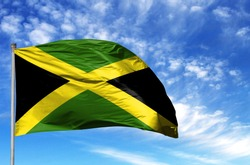 National flag of Jamaica on a flagpole in front of blue sky