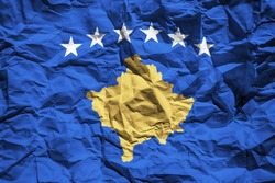 National flag of Kosovo on crumpled paper. Flag printed on a sheet. Flag image for design on flyers, advertising.