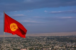 National flag of Kyrgyzstan on the background of the city of Osh