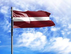 National flag of Latvia on a flagpole in front of blue sky.