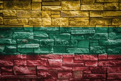 National flag of Lithuania on stone  wall background.The concept of national pride and symbol of the country. Flag  banner on  stone texture background.