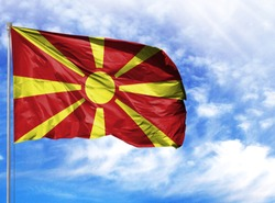 National flag of Macedonia on a flagpole in front of blue sky