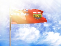 National flag of Manitoba on a flagpole in front of blue sky