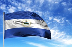 National flag of Nicaragua on a flagpole in front of blue sky