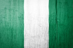 National flag of Nigeria depicting in paint colors on old textile. Flag  banner on  fabric texture background.