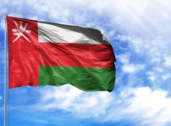 National flag of Oman on a flagpole in front of blue sky