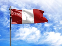 National flag of Peru on a flagpole in front of blue sky.