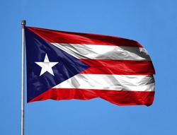 National flag of Puerto Rico on a flagpole in front of blue sky