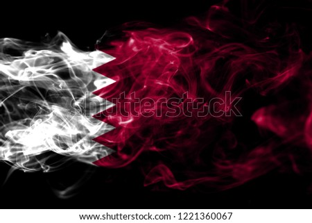 National flag of Qatar made from colored smoke isolated on black background. Abstract silky wave background
