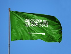 National flag of Saudi Arabia on a flagpole in front of blue sky