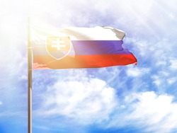 National flag of Slovakia on a flagpole in front of blue sky