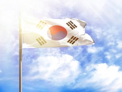 National flag of South Korea on a flagpole in front of blue sky