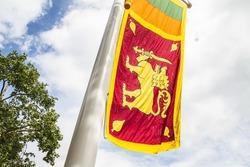 National Flag of Sri Lanka (the Sinha Flag or Lion Flag) fluttering on a pole.